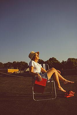 Junge Frau sitzt entspannt mit Buch auf Hausdach - p432m2260321 von mia takahara