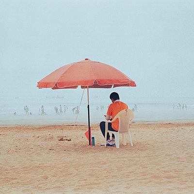 Mann unter einem Sonnenschirm am Strand - p817m2291137 von Daniel K Schweitzer