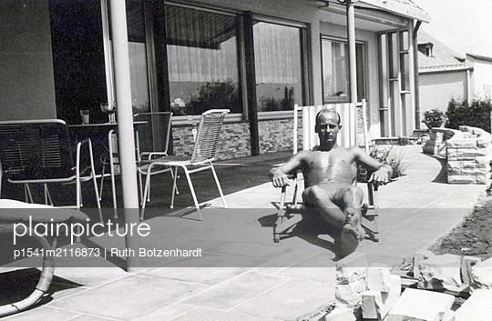 Junger Mann beim Sonnenbad auf der Terrasse - p1541m2116873 von Ruth Botzenhardt