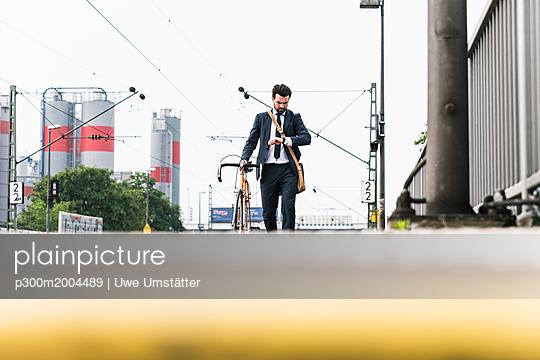 Businessman with bicycle waiting at the platform - p300m2004489 von Uwe Umstätter