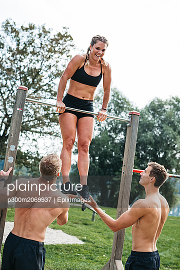 Sportive team during workout, men helping woman on bar, outdoor - p300m2069937 by Epiximages