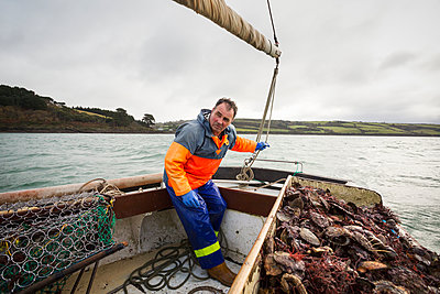 Traditional sustainable oyster fishing. A fisherman on a sailing boat sorting the oyster catch  - p1100m1216020 by Mint Images