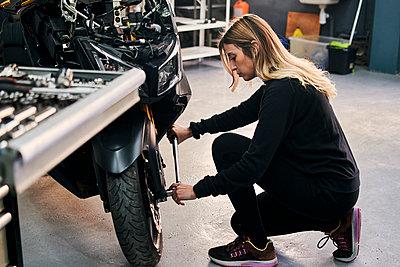 Mechanic woman works in a garage repairing a motorcycle - p1166m2268338 by Cavan Images