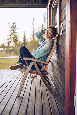 Sweden, Lapland, portrait of young woman sitting on chair on veranda relaxing - p300m2059315 by CSSHOT