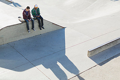 View from above of two teenage boys at skate-park. - p328m784005f by Hero Images