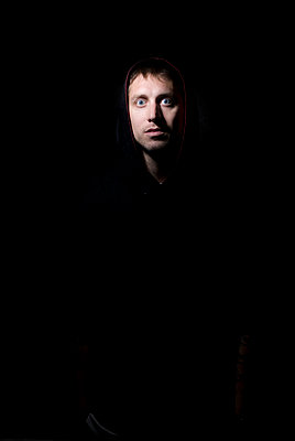 Portrait of young man with blue eyes and  a hood on with a scared facial expression on black backdrop - p343m964116 by Jon Paciaroni