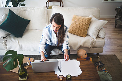 High angle view of female entrepreneur concentrating on work while daughter playing at home office - p426m2117040 by Maskot