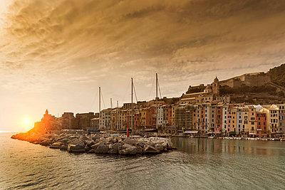 View of harbour and Church of St Peter on headland at sunset, Porto Venere, Liguria, Italy - p429m1417561 by WALTER ZERLA