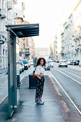 Woman standing at bus stop, Milan, Italy - p429m1513679 by Eugenio Marongiu