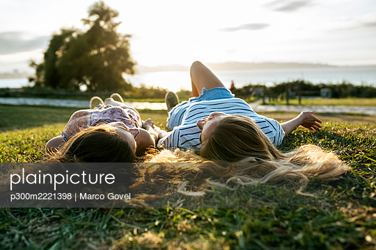 Young female friends relaxing on field while spending weekend together - p300m2221398 by Marco Govel