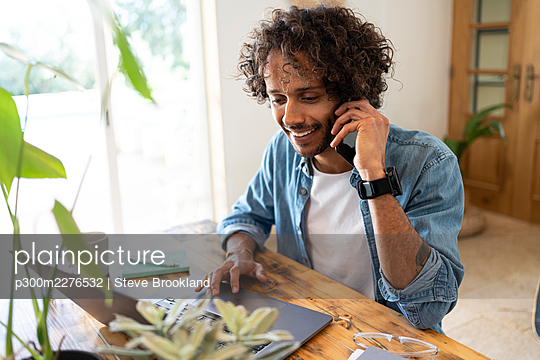 Male entrepreneur talking on smart phone while using laptop at home - p300m2276532 by Steve Brookland