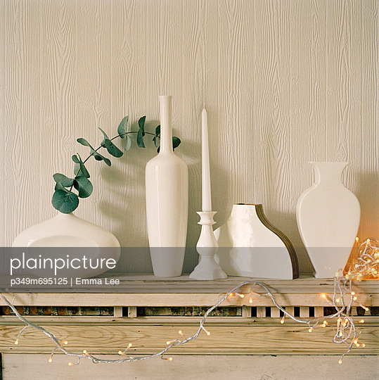 Detail of white vases and Christmas decorations on a wooden mantelpiece - p349m695125 by Emma Lee
