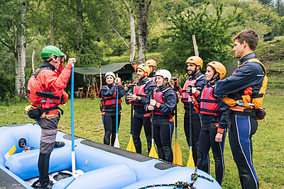 Instructor talking to group of friends at a rafting class - p300m2114186 by Francesco Buttitta