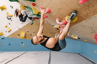Man and woman bouldering in climbing gym - p300m2169863 by Hernandez and Sorokina
