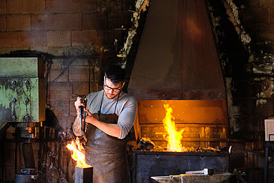 Young male blacksmith burning metal in fire at workshop - p300m2281446 by Antonio Ovejero Diaz