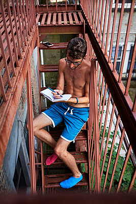 Caucasian man sitting on urban fire escape writing in journal - p555m1303232 by Granger Wootz