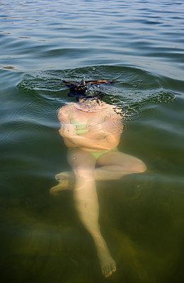 Netherlands, Noord-Brabant, Breda, Woman submerging in lake - p924m2292512 by Mischa Keijser