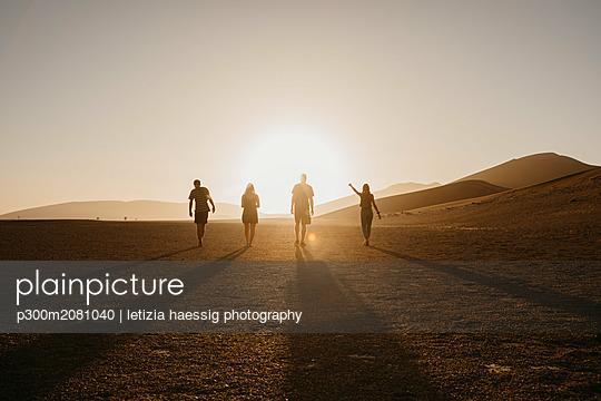 Namibia, Namib desert, Namib-Naukluft National Park, Sossusvlei, friends walking at Dune 45 at sunrise - p300m2081040 by letizia haessig photography
