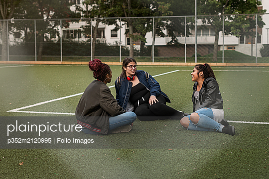Teenage girls sitting on tennis court - p352m2120995 by Folio Images