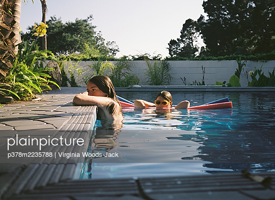 Two girls in pool - p378m2235788 by Virginia Woods-Jack