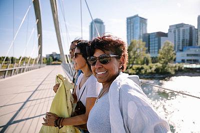 Portrait smiling, confident mature woman with friends on sunny, urban bridge - p1192m2130095 by Hero Images