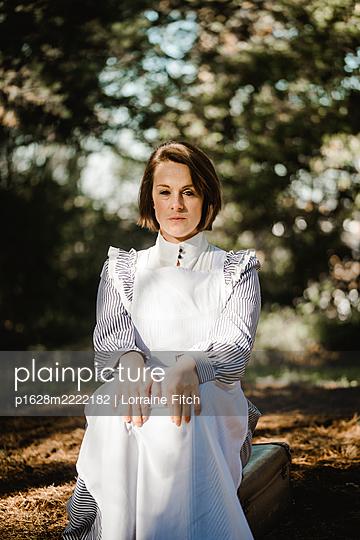 Frau in Dienstmädchenkleidung im Park, Portrait - p1628m2222182 von Lorraine Fitch