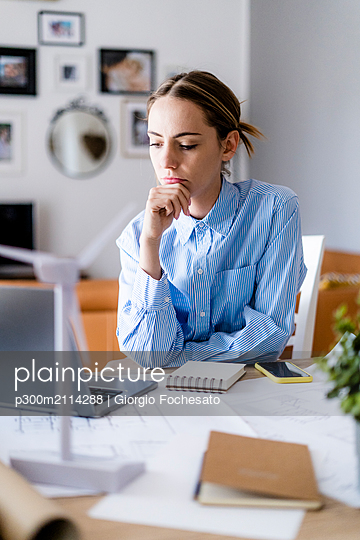 Woman in office working on plan and laptop with wind turbine model on table - p300m2114288 von Giorgio Fochesato