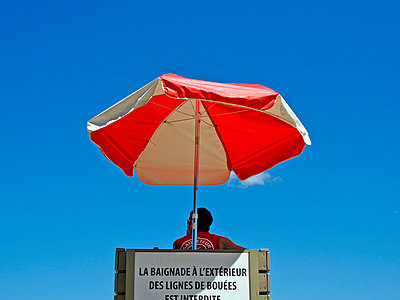 Lifeguard seated under umbrella in lifeguard chair - p1072m830491 by Clive Branson