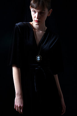 Woman in Black Dress with Cameo Necklace - p1248m2122143 by miguel sobreira
