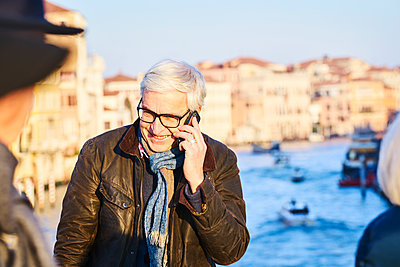 Man is phoning on a bridge in Venice - p1312m2082167 by Axel Killian