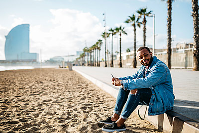 Spain, Barcelona, smiling young traveler sitting at the beach - p300m1204608 by Josep Rovirosa