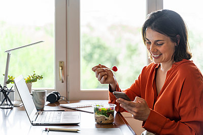 Smiling business person using mobile phone while eating salad at home - p300m2206515 by VITTA GALLERY