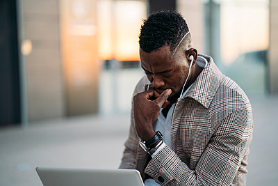 Man using laptop while listening to music - p300m2256372 by Manu Padilla Photo