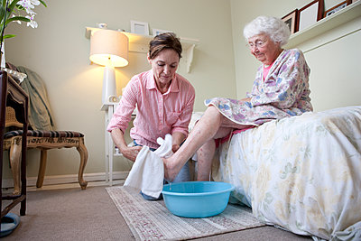 Caregiver washing foot of older woman in bedroom - p555m1408837 by Shestock