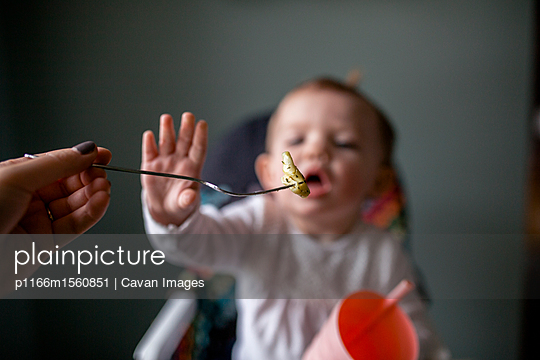 Cropped hand of mother feeding food to daughter at home - p1166m1560851 by Cavan Images