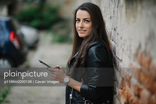Young woman is smiling and holding phone by the brickwall. - p1166m2200106 by Cavan Images