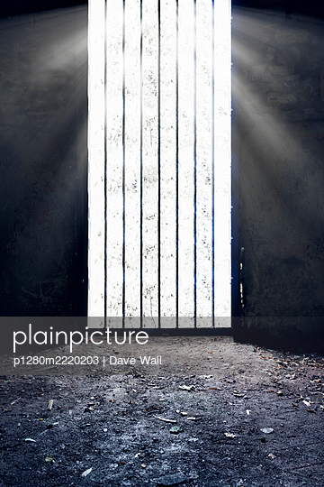 Trellised prison cell with dirt floor and sunbeams - p1280m2220203 by Dave Wall