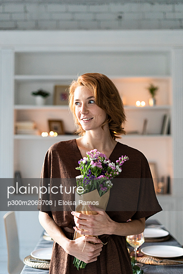 Redheaded woman holding bunch of flowers, standing in front of laid table - p300m2069708 by Eloisa Ramos