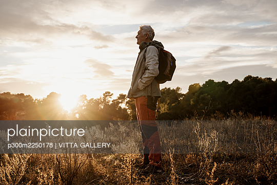 Senior male hiker with hands in pockets enjoying sunset view at agricultural field - p300m2250178 by VITTA GALLERY