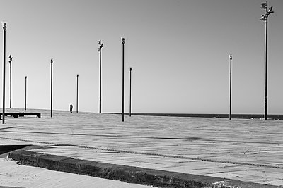 Man walking in sidewalk among the shore - p1166m2137498 by Cavan Images