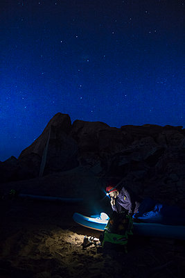 View of woman on sleeping bag under night sky, Utah, USA - p1166m2202304 by Suzanne Stroeer