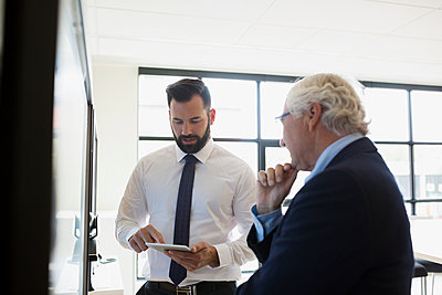 Businessmen using digital tablet in conference room - p1192m1173759 by Hero Images