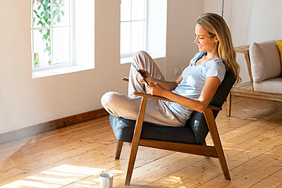 Smiling woman using digital tablet while sitting on chair in living room - p300m2276436 by Steve Brookland
