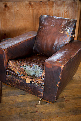 An old weathered leather armchair with torn cushion - p30119685f by Tobias Titz