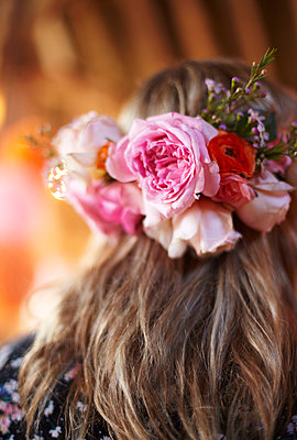 Woman wears garland of pink roses in her hair  late summer. - p349m2167856 by Sussie Bell
