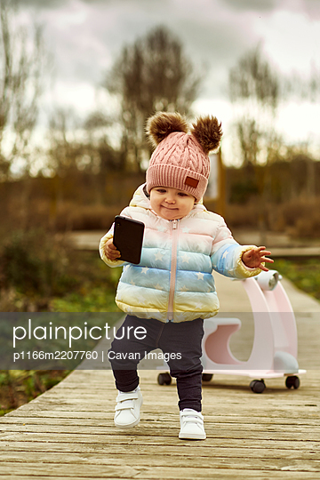 A 1 year old baby girl is with a pink motorcycle outside - p1166m2207760 by Cavan Images
