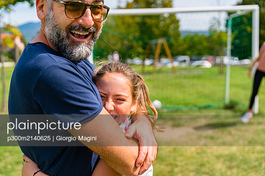 Happy father and daughter hugging on a football pitch - p300m2140625 by Giorgio Magini