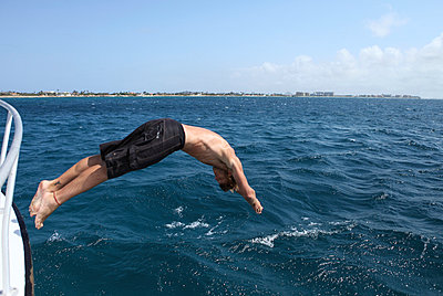 Man jumping into the water - p045m926012 by Jasmin Sander