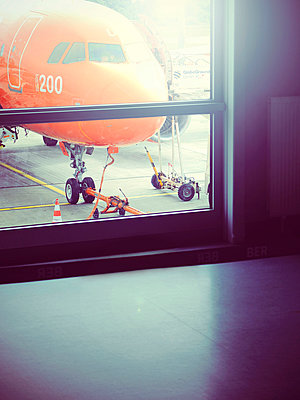 Parked jet through terminal window - p1072m941445 by Neville Mountford-Hoare