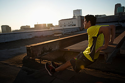 A man in exercise clothes on a rooftop overlooking the city, doing bench shoulder push ups.  - p1100m1107172 by Mint Images